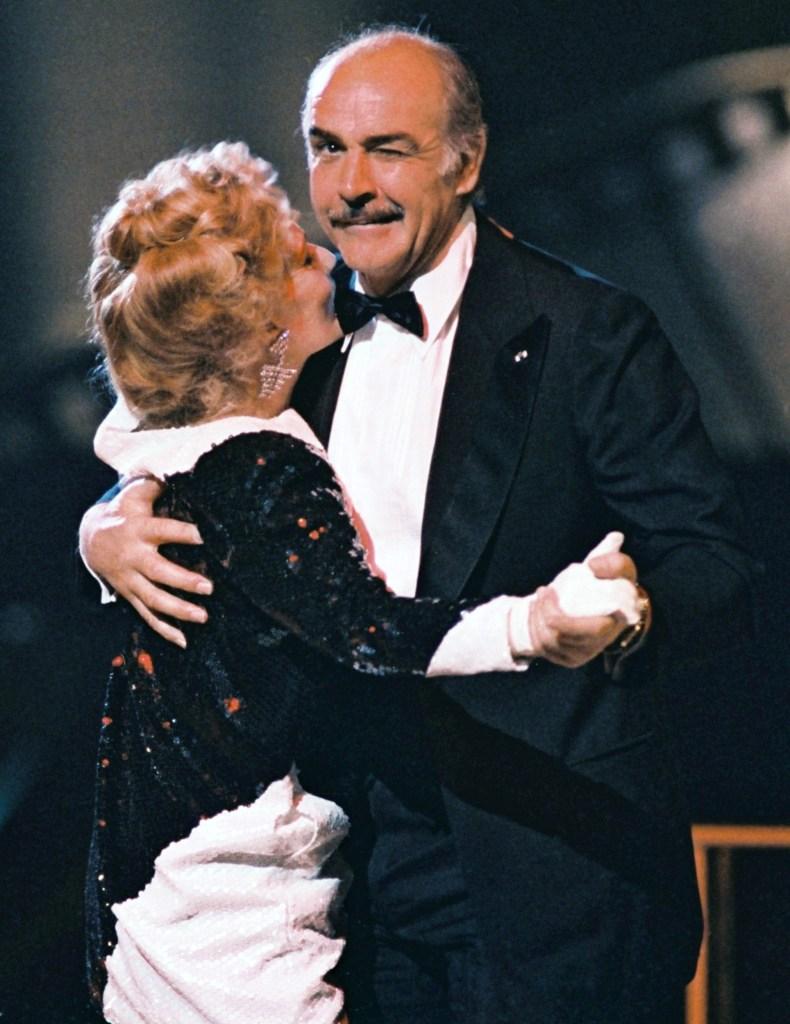 En esta foto de archivo tomada el 7 de marzo de 1987, el actor británico Sean Connery, presidente de la XII edición de los Premios César de la Academia Francesa, le hace un guiño al fotógrafo mientras baila en París con la actriz francesa Jeanne Moreau, la ceremonia anual de premios de la industria cinematográfica francesa. (Foto MICHEL GANGNE / AFP)