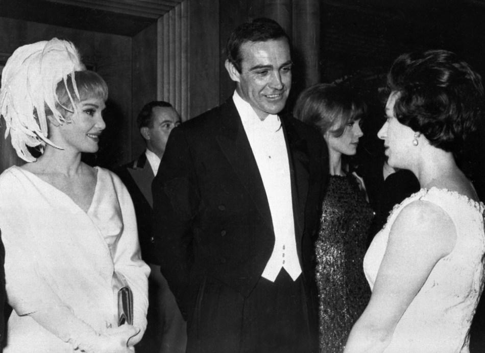 """El actor Sean Connery y su esposa, la actriz estadounidense Diane Cilento, se presentan a la princesa Margaret, el 15 de febrero de 1965, durante el Royal Film Performance de """"Lord Jim"""". (Foto por - / AFP)"""