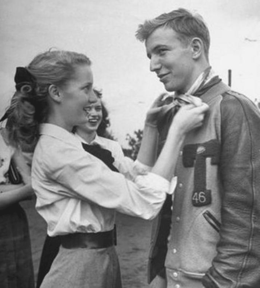 Young man with 1950s letter jacket and young woman
