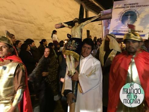hombre en túnica blanca sosteniendo crucifijo en procesión de semana santa