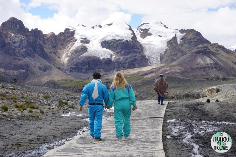 Pareja de turistas vestidos para la nieve en contraste de un local con poncho, en el camino del Nevado Pastoruri. Huaraz y la Corillera Blanca