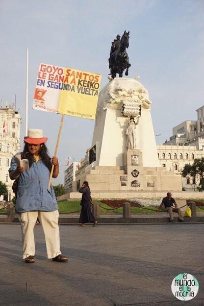 Hombre con pelo largo y cartel político frente a la estatua de San Martín en la Plaza San Martín en Lima Perú
