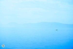 Amanece en la costa de la Isla Hvar. La niebla lo cubre todo excepto un pescador y su barca