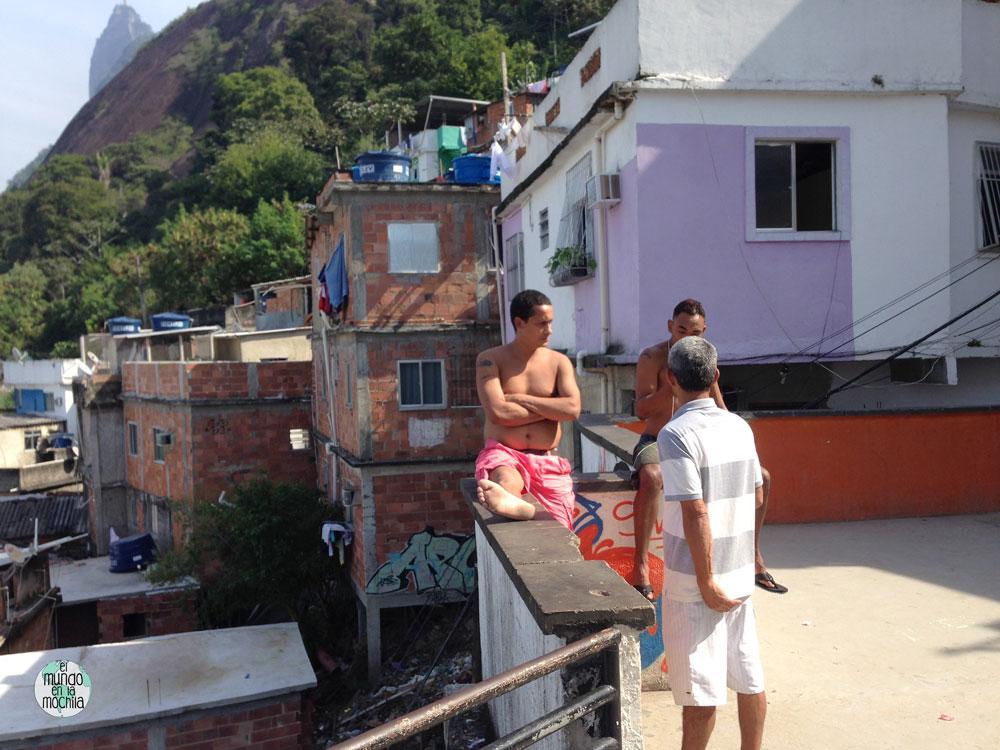 Tres hombres conversan tranquilamente en el mirador de Michael Jackson, en la favela Santa Marta