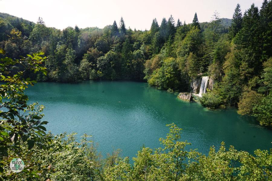 Cascada cae sobre una laguna aguamarina rodeada por el bosque en Parque Nacional de los Lagos de Plitvice