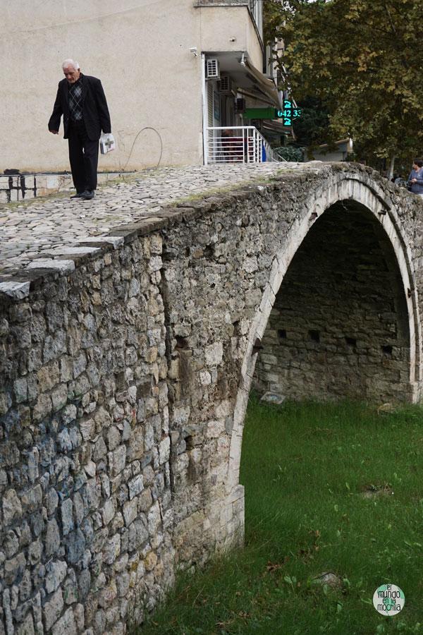 Un señor camina sobre el puente viejo de Tirana, Albania