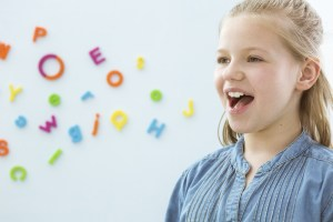 girl opening mouth in speech therapy office