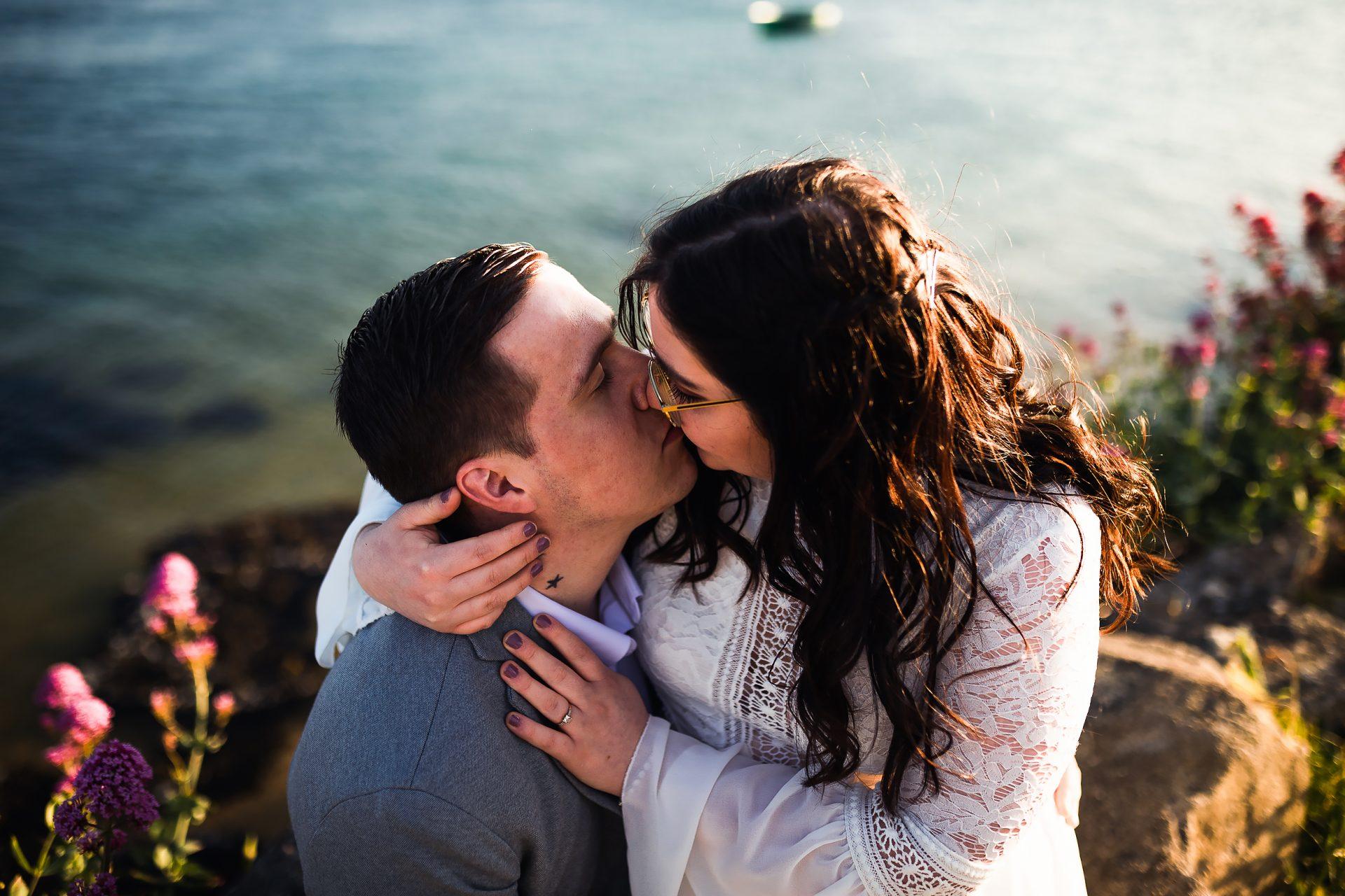 couple de futurs mariés qui s'embrassent en bord de mer.