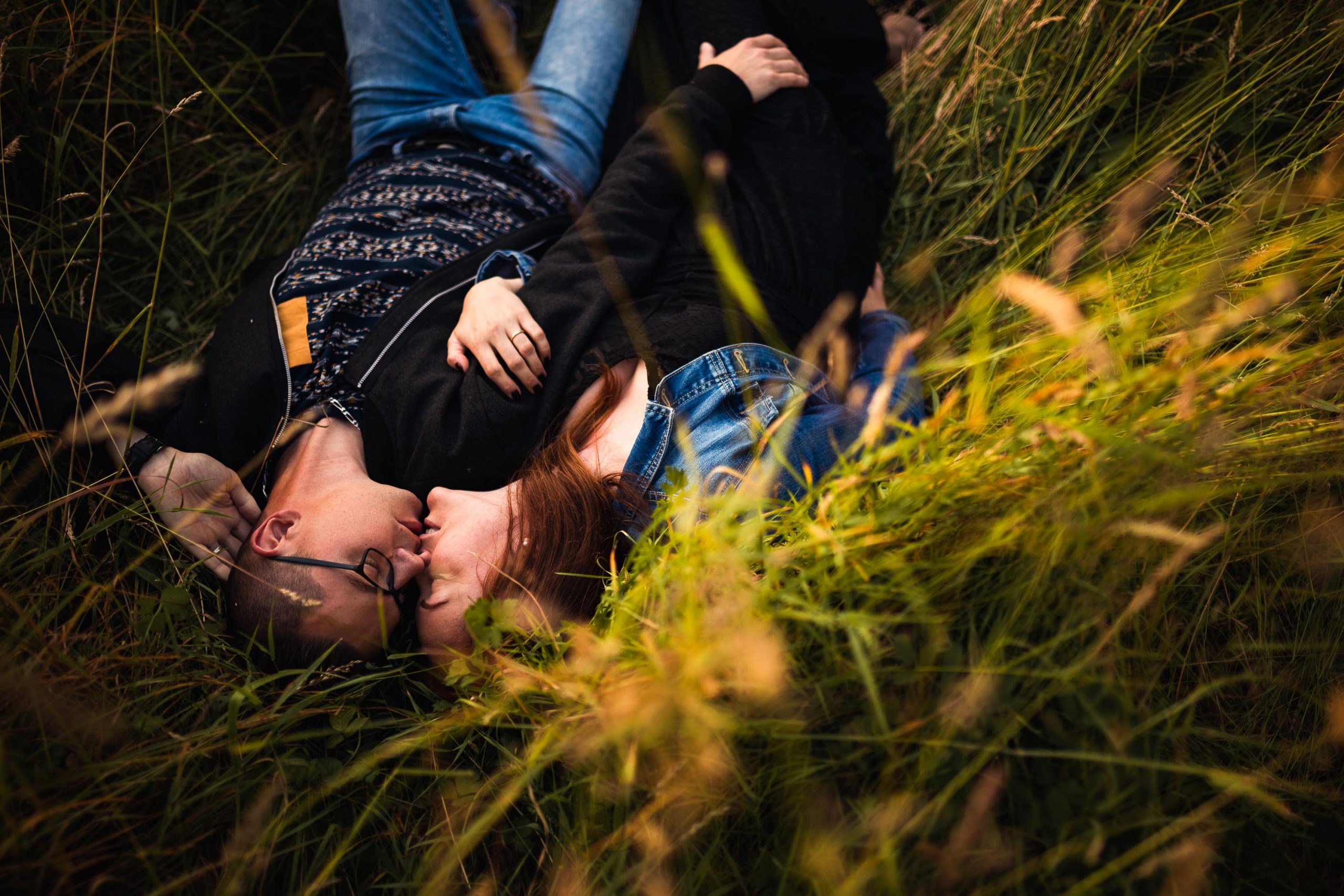 Photographie d'un couple allongé dans l'herbe.