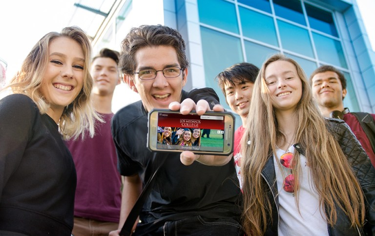 Students showing a responsive website on a phone