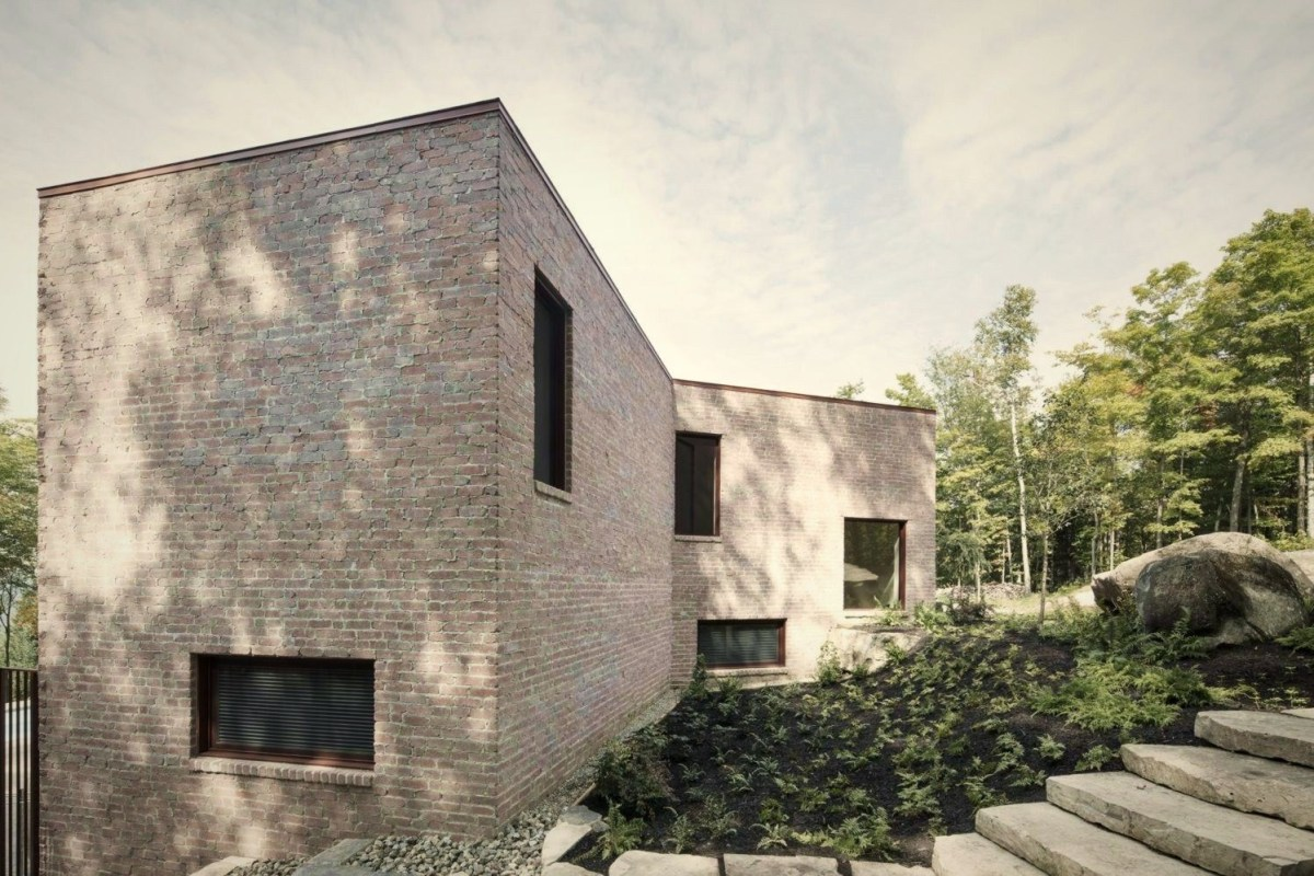 Futurist house design Les Elves in Quebec with box house style and lots of large windows build on sloping land (5)