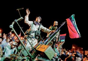 Manifestantes en contra de Gadafi, portando la bandera monárquica del anterior gobernante, Idris I