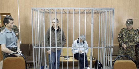 Fotografía de Khodorkovsky, de pie a la izquierda de la fotografía, durante su juicio en Moscú.