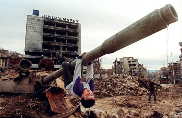 Un niño juega en el cañón de un tanque destruido y abandonado en las calles de Sarajevo en abril de 1996. Fotografía de AFP y Odd Andersen