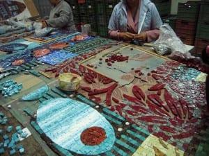 Los artesanos en Permono trabajan con pequeños pedazos de cristal para formar los diseños de lo que será el pavimento.