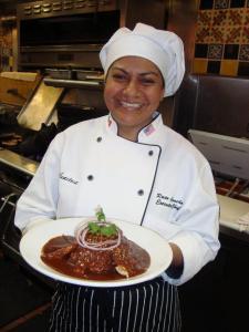 Con una hermosa sonrisa, la Chef Rocío Camacho muestra orgullosa una de sus creaciones culinarias.