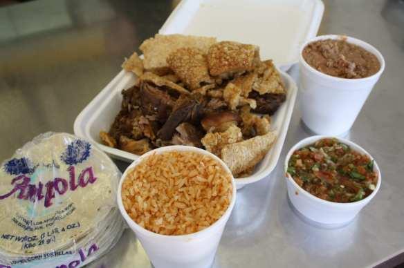 El paquete familiar de carnitas es económico y muy llenador con su arroz rojo, salsa mexicana, frijoles refritos y tortillas. (Foto de Agustín Durán/El Pasajero).