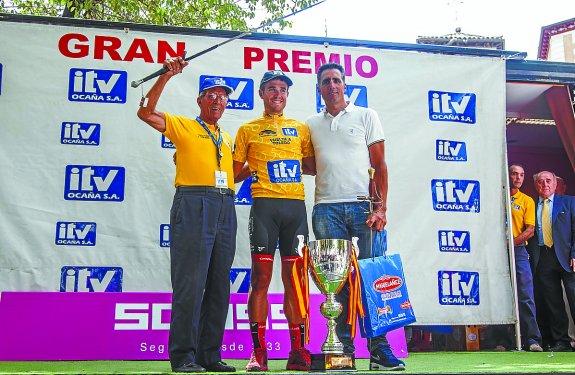 GRA113. TOLEDO, 11/08/2015.- El ganador de la clasificación general de la Vuelta Ciclista a Toledo, Mikel Aristi (c), posa en el podio junto a los exciclistas Federico Martín Bahamontes (i) y Miguel Induráin (d), al término de la competición hoy en la plaza del Zocodover, en Toledo. EFE/Héctor Martín