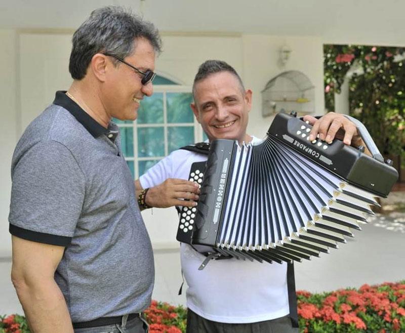 El Rey Vallenato Julián Rojas, tocando el regalo que le llevó el Presidente de la Fundación Festival de la Leyenda Vallenata, Rodolfo Molina Araújo.