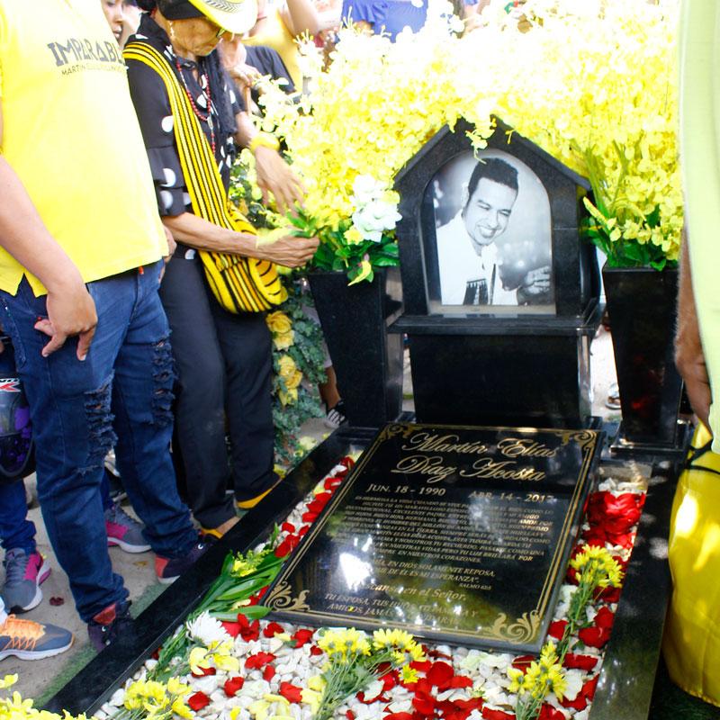 La tumba del artista la colmaron de flores amarillas, pétalos color rojo y blanco.