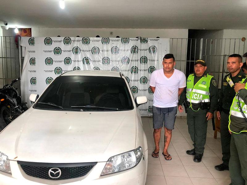 El detenido junto con el carro recuperado.