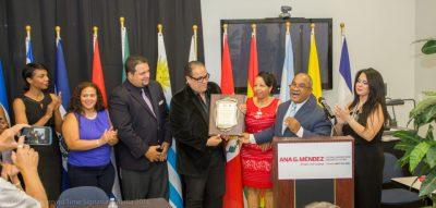 El destacado locutor dominicano, Edwin Bautista, recibe la placa de reconocimiento por parte de Olivo de León, presidente del CDP y miembros de la seccional en la Florida, adjunto a Daniel Betancourt, director asociado de SUAGM. Observa la maestra de ceremonias, Dryalis Muñoz.