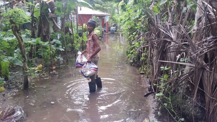 familia-recibe-ayuda-del-plan-social-en-medio-de-inundacion