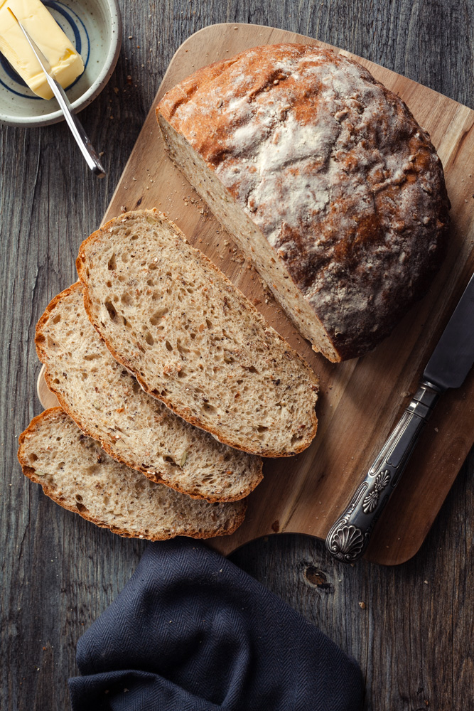 Six seed rustic bread, sliced on a wooden board with butter dish