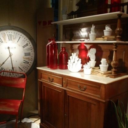 Alacena antigua restaurada, reloj y sillas de estilo industrial.
