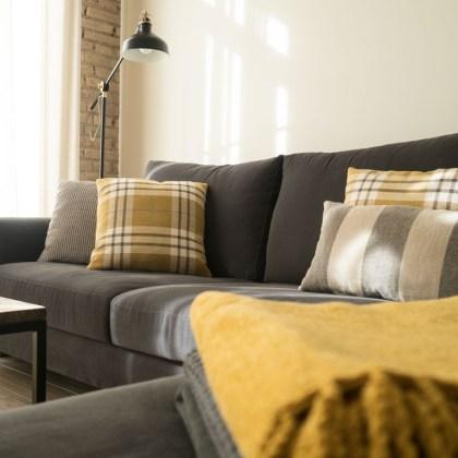 sofá gris con cojnes de diseño tonos tierra