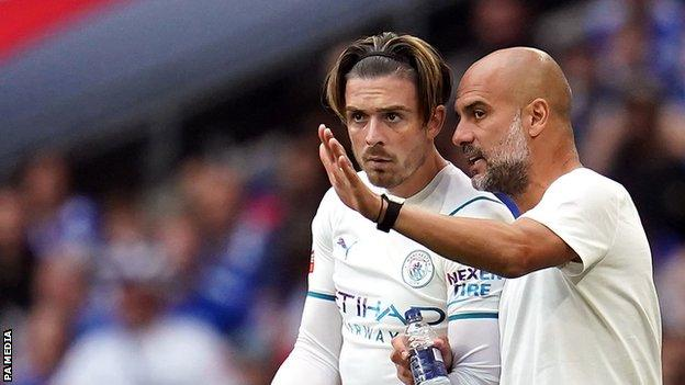Manchester City manager Pep Guardiola speaks to Jack Grealish as he comes off the bench