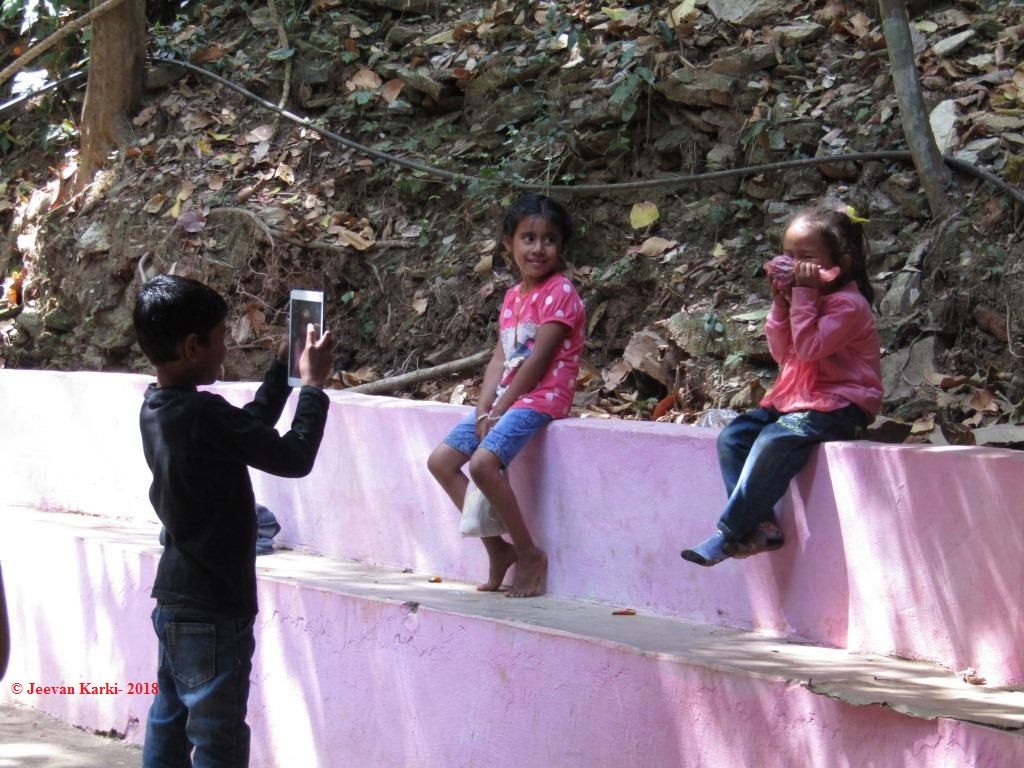 Children clicking the photo using mobile phone in a travel.