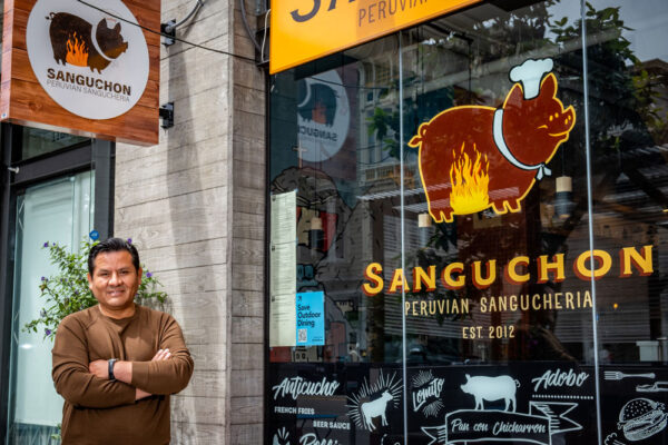 A man poses for a portrait. He is on the left and on the right is the window of the restaurant with the logo