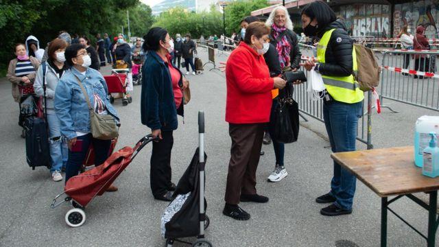 Gente haciendo fila en un banco de alimento de Ginebra en junio pasado.