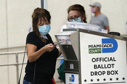 Una mujer deposita un voto por correo en Miami. Cada estado tiene sus propias reglas y plazos para el proceso electoral (AP)