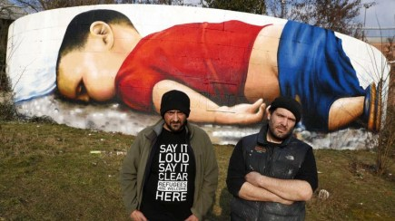 Artists Justus Becker (R) and Oguz Sen stand in front of a huge graffiti artwork of Syrian toddler Aylan Kurdi, after finishing a three-day painting session on a wall on the banks of river Main near the headquarters of the European Central Bank in Frankfurt, Germany, March 10, 2016. REUTERS/Kai Pfaffenbach