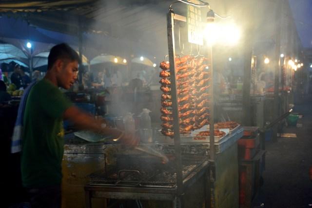 Kota Kinabalu, Malaysia--Local people selling BBQ chicken in Kota Kinabalu night market by the seafront in Sabah Borneo Malaysia.