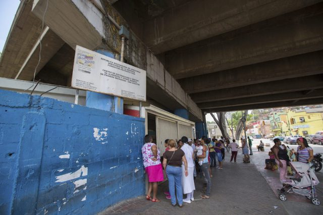 An unidentified group of people waiting in line at a public supermarket doors in Caracas. With significant inflation, rationing is required in some places in Venezuela in 2015 .