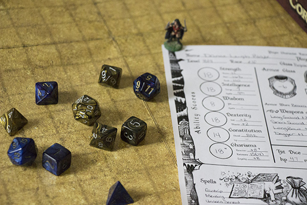 A role-playing game character sheet, miniature, and dice