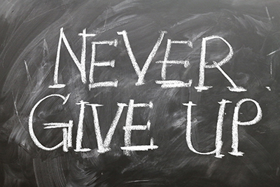 Never give up written on chalkboard