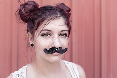 Girl wearing a black fuzzy mustache.