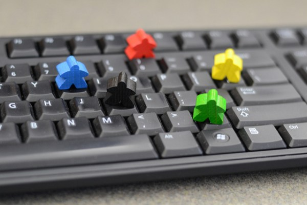5 Meeples standing on Keyboard