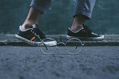 Round glasses on street next to feet