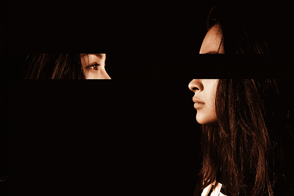 Two women looking at one another, one with her eyes missing the other with only her eyes showing