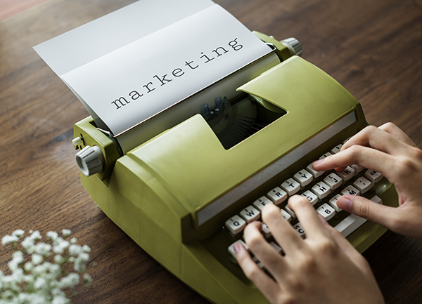 green typewriter with word marketing on paper
