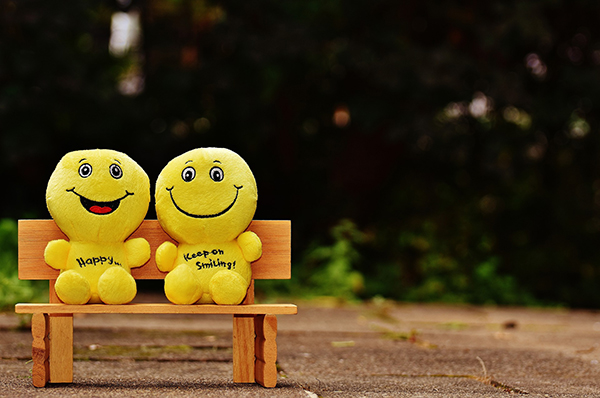 two smilies stuffed toys sitting on bench