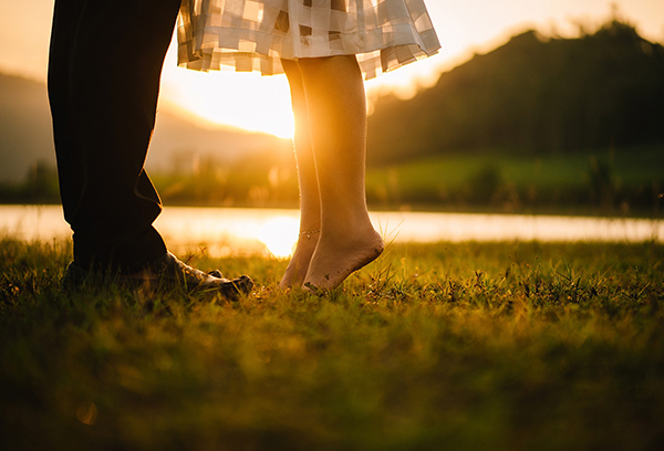Couple's legs by lake at sunset