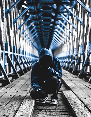 Man squatting in hoodie