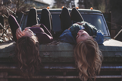 Two girls lying on an old truck