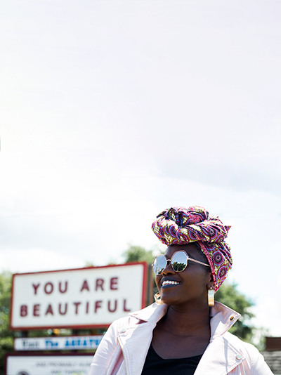 Woman standing in front of sign that says You are Beautiful